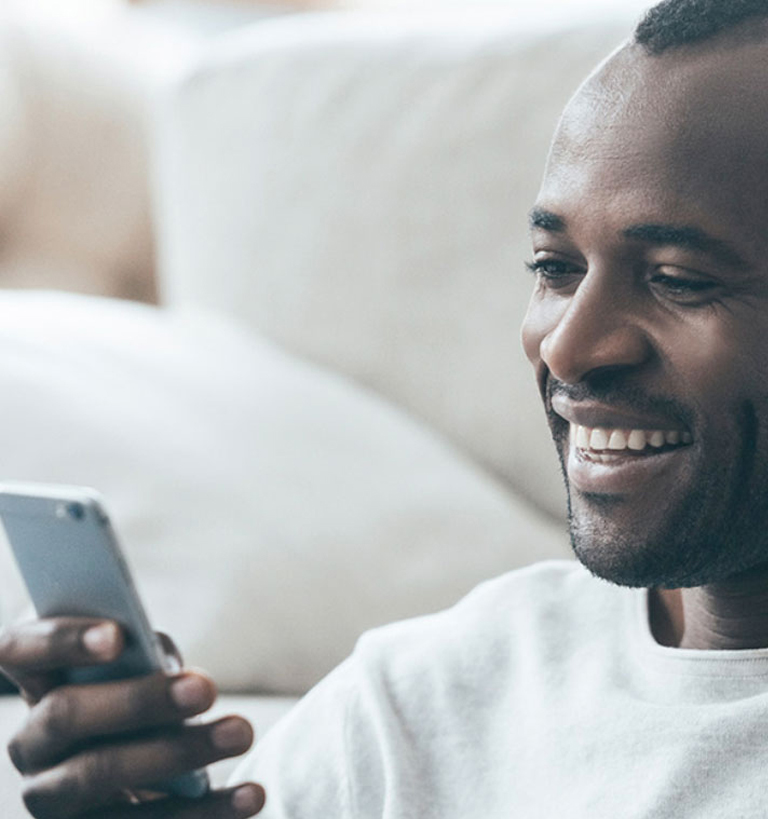 A man sitting on a couch smiling at his phone.