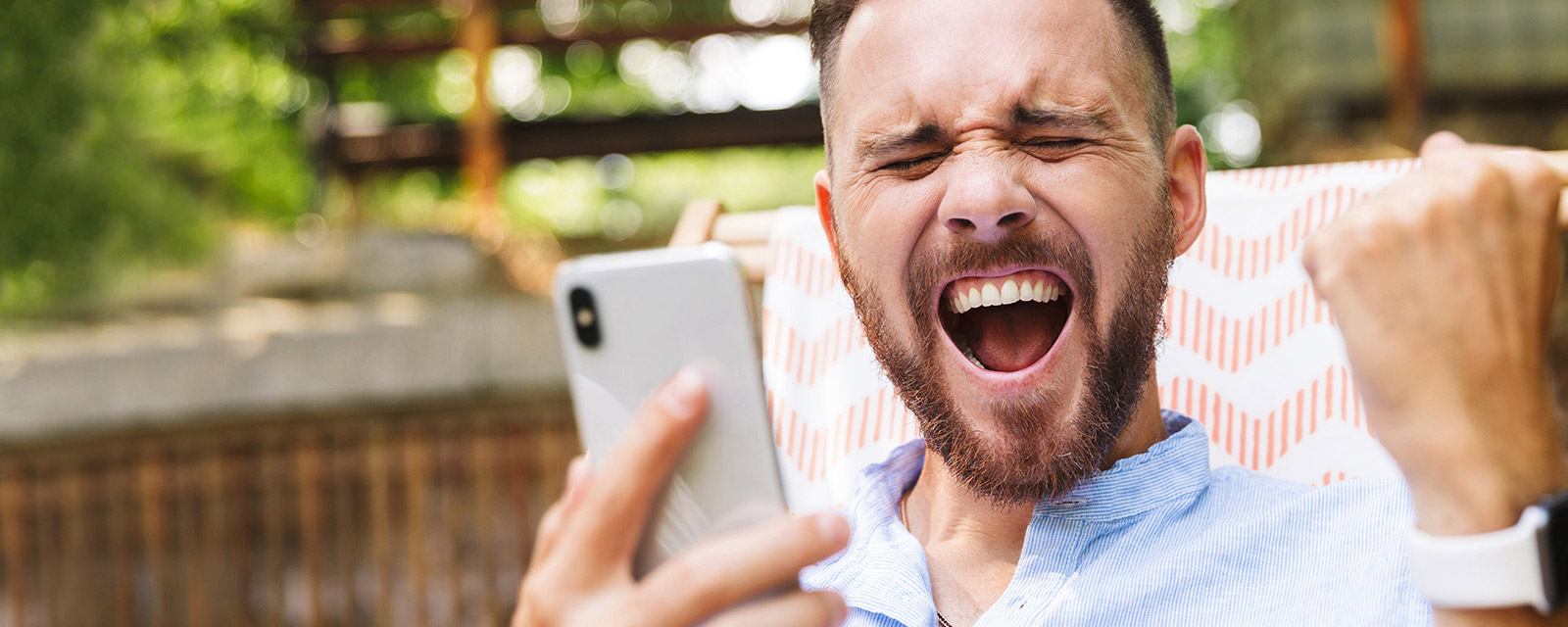 A man with a happy expression holding a phone.