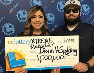 A couple holding a million dollar check